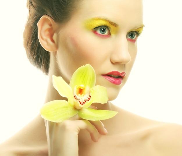 Zamknij się portret młodej kobiety z jasnym makijażem, trzymając orchideę