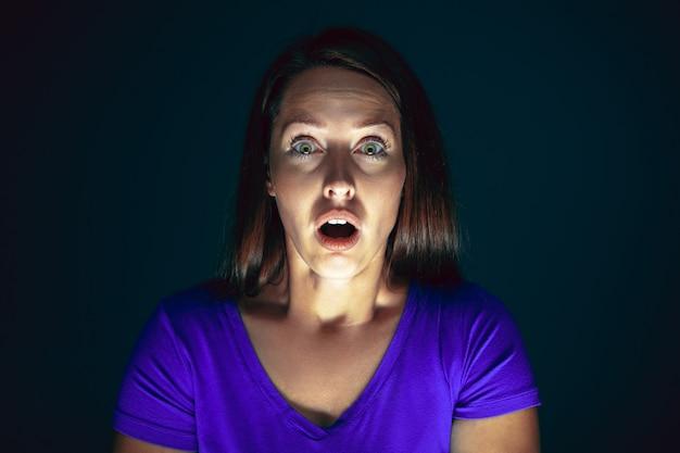 Zamknij się portret młodej szalonej przestraszonej i zszokowanej kobiety odizolowanej na czarno