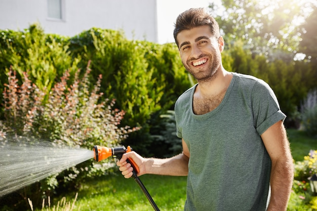 Zamknij się portret na zewnątrz młody przystojny kaukaski mężczyzna ogrodnik uśmiechnięty podlewanie roślin, spędzając lato w wiejskim domu.