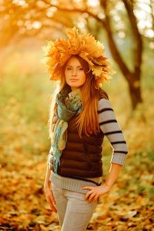Zamknij się portret pięknej dziewczyny w niebieskiej kamizelce, stoi na tle bajecznej jesieni. na głowie jest bujny wieniec z jesiennych liści.