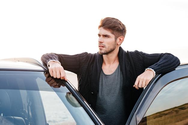 Zamknij się portret przypadkowego młodego mężczyzny stojącego w pobliżu jego samochodu na zewnątrz