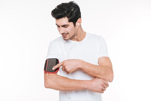Zamknij się portret szczęśliwego młodego sportowca za pomocą pustego ekranu telefonu komórkowego na opasce na białym tle na białym tle
