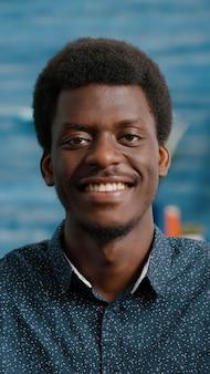 Zamknij się portret uroczego przystojnego afroamerykanina uśmiechającego się do kamery