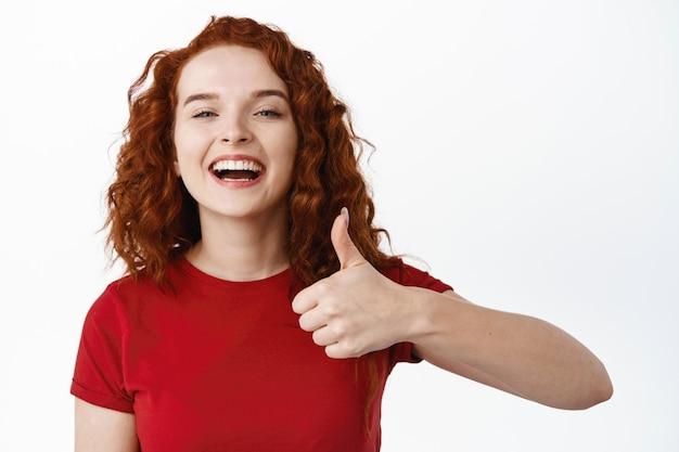 Zamknij się portret wesołej i pozytywnej rudej dziewczyny z kręconymi długimi włosami, pokazując kciuk w górę z aprobatą i powiedz tak, polecam dobrą rzecz, pochwal produkt, biała ściana