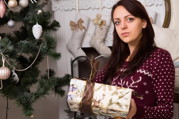 Zamknij się poważna młoda kobieta w bordowej koszuli z długim rękawem, trzymając pudełko w pobliżu choinki, patrząc w kamerę.