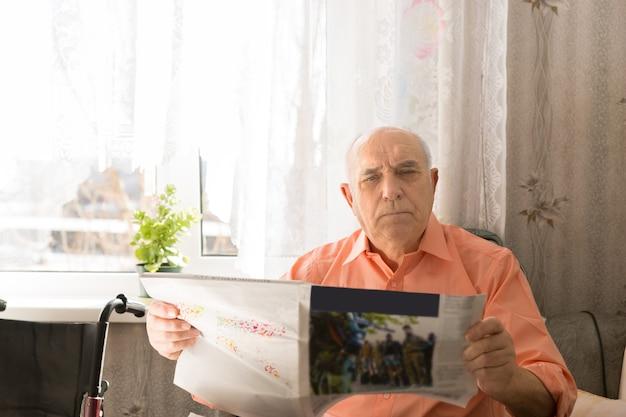 Zamknij się poważny starszy mężczyzna trzyma tabloid patrząc na kamery, siedząc w swoim domu.