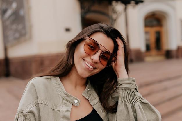Zamknij się poza portret uroczej atrakcyjnej kobiety noszącej okulary przeciwsłoneczne, uśmiechając się i chodząc po mieście wiosną
