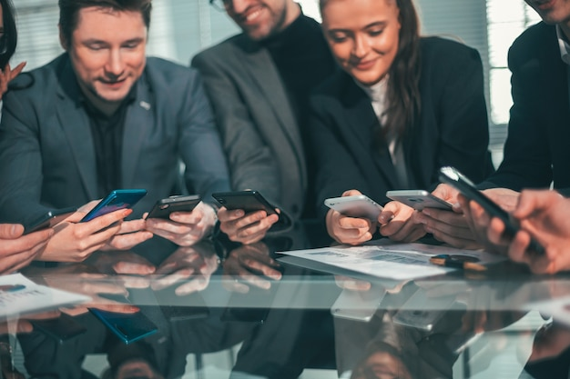 Zamknij się. pracownicy ze smartfonami siedzący przy biurku. ludzie i technologia