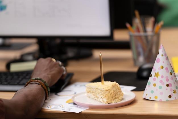 Zamknij się pracownik z ciastem i kapeluszem na przyjęcie