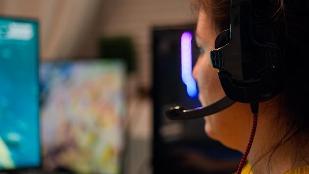 Zamknij się pro dziewczyna gra komputerowa strzelanka fps na mistrzostwach, rozmawiając z zestawem słuchawkowym. esportowa drużyna graczy gra w makietę gry wideo, występując w stylowym cyber-pokoju.