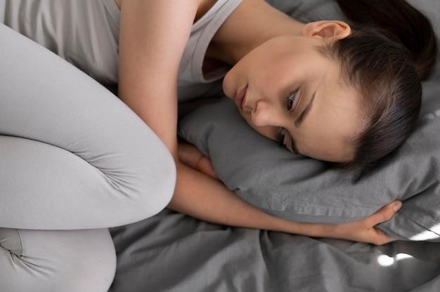 Zamknij się przygnębiona kobieta w łóżku