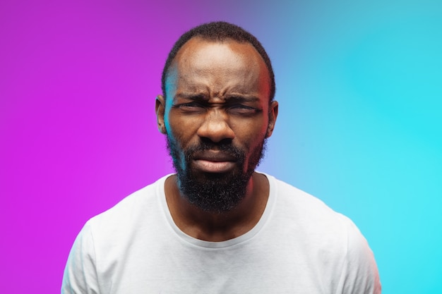 Zamknij się przypatrując. afro-portret młodego mężczyzny na gradientowym tle w neon. piękny męski model w stylu casual, biała koszula. pojęcie ludzkich emocji, wyraz twarzy, sprzedaż, reklama.