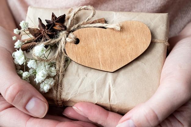 Zamknij się pudełko zawinięte w papier rzemieślniczy ozdobiony drewnianym sercem i białymi kwiatami w rękach