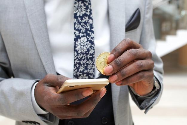 Zamknij się rąk z monetą kryptowaluty btc i smartfonem.