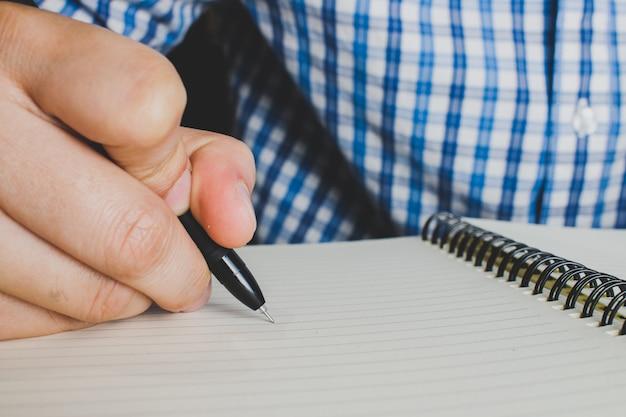 Zamknij się, ręka mężczyzny pisze piórem.