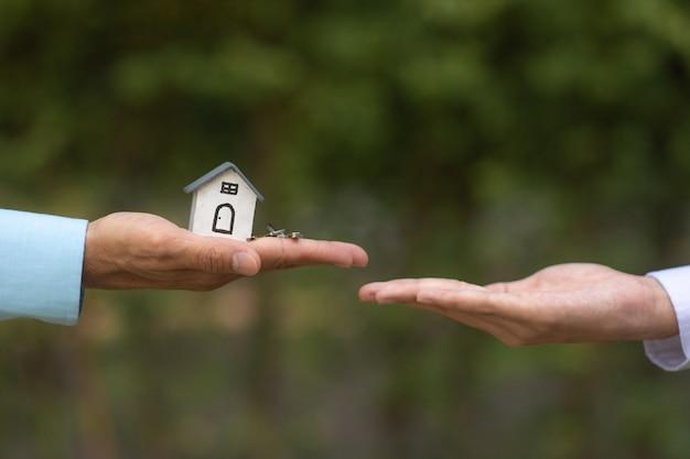 Zamknij się ręka, podając klucz i model domu w koncepcji sprzedaży ubezpieczenia czynszu inwestycyjnego nieruchomości