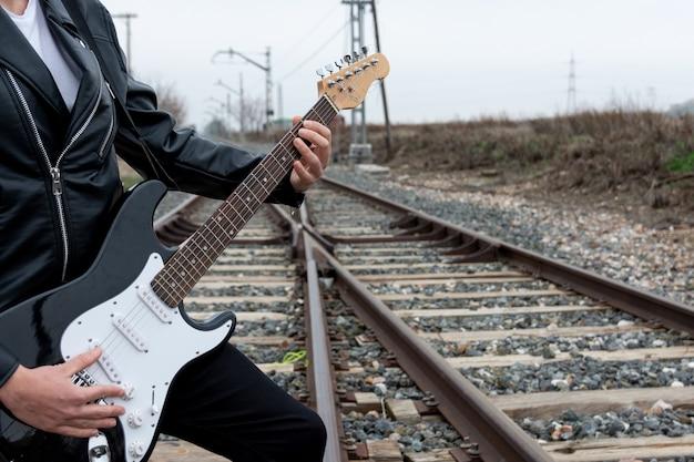 Zamknij się rocker z okulary gra na gitarze elektrycznej na opuszczonych torach kolejowych.