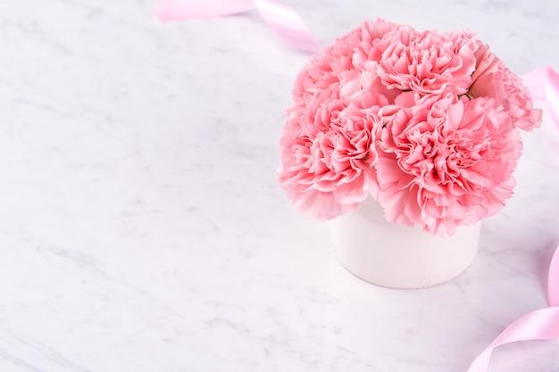 Zamknij się różowy goździk na białym tle marmuru na dzień matki fower