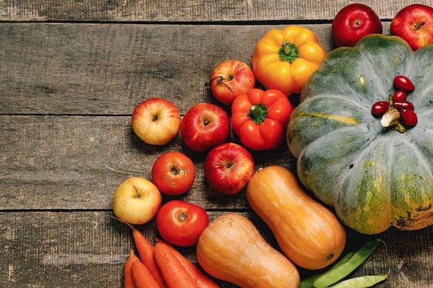 Zamknij się rozrzuconych warzyw dyni, pieprzu i jabłek na stole