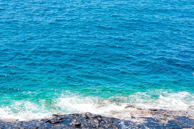 Zamknij się skaliste wybrzeże z krystaliczną wodą