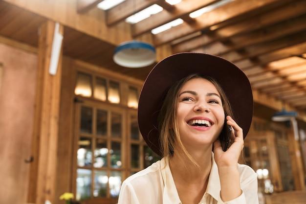 Zamknij się śmiejąca się kobieta w kapeluszu siedzi w kawiarni
