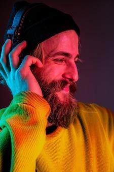 Zamknij Się, Spokojnie. Portret Mężczyzny Rasy Kaukaskiej Na Tle Gradientu Studio W świetle Neonu. Piękny Męski Model W Stylu Hipster W Słuchawkach. Pojęcie Ludzkich Emocji, Wyraz Twarzy, Sprzedaż, Reklama. Darmowe Zdjęcia