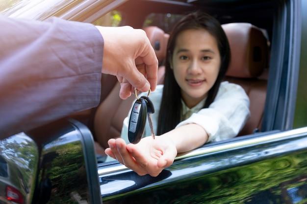 Zamknij się sprzedawcy, podając klucz do nowego samochodu właściciela. nowe auto. dealer samochodów daje kobiecie klucz samochodowy do jazdy próbnej na wiejskiej drodze.