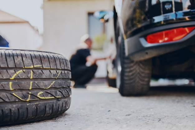Zamknij się stare opony na ziemi w warsztacie auto mechanik.