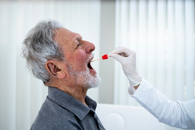 Zamknij się starszy mężczyzna robi badanie gardła pcr w biurze lekarzy podczas epidemii wirusa koronowego