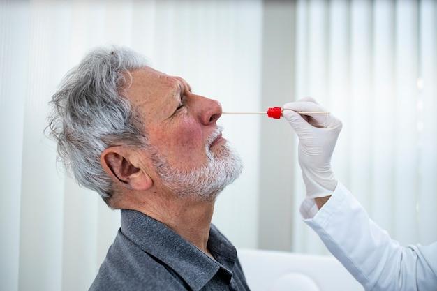 Zamknij się starszy mężczyzna robi badanie nosa pcr w biurze lekarzy podczas epidemii wirusa koronowego