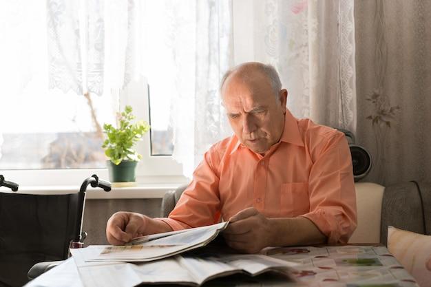 Zamknij się stary łysy mężczyzna czytający najnowsze wiadomości w tabloidzie, siedząc w salonie przy oknie.