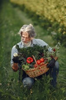 Zamknij się stary rolnik posiadający kosz warzyw. mężczyzna stoi w ogrodzie. senior w czarnym fartuchu.