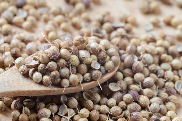 Zamknij się stos nasion kolendry i drewnianą łyżką