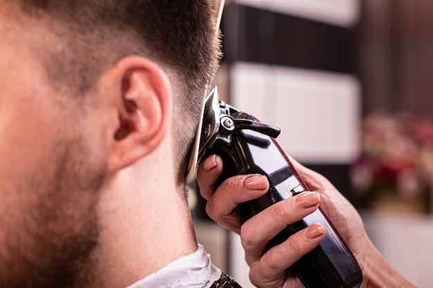 Zamknij się studentka o strzyżenie z maszynką do strzyżenia włosów