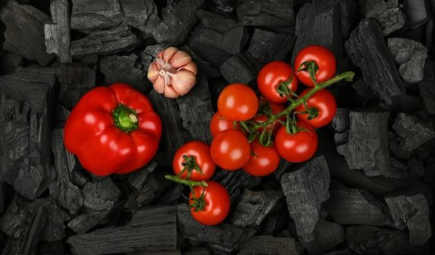 Zamknij się surowa czerwona papryka na czarne kawałki węgla drzewnego bryłek gotowy do gotowania z grilla grill, podwyższone widok z góry, bezpośrednio powyżej
