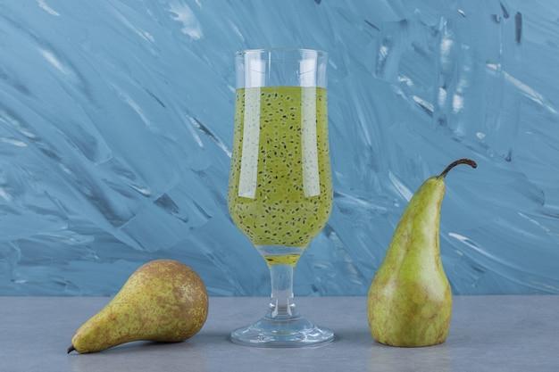 Zamknij się świeże gruszki i sok na szarej powierzchni