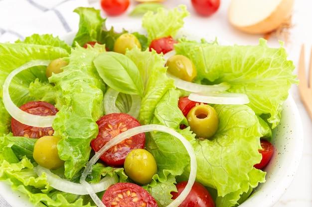 Zamknij się świeże i zdrowe sałatki z sałatą, cebulą, pomidorem cherry i oliwkami w misce. jedzenie środziemnomorskie