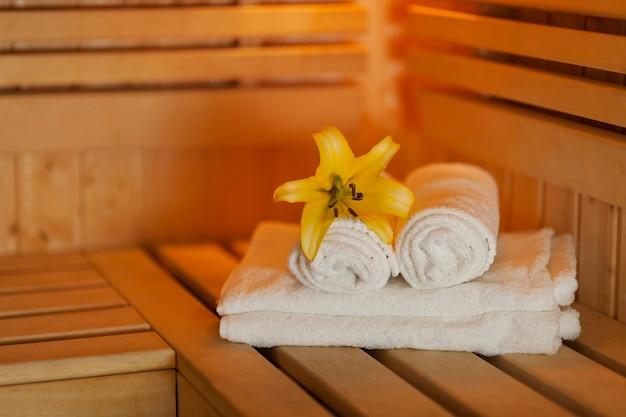 Zamknij się świeże ręczniki i żółta lilia w saunie