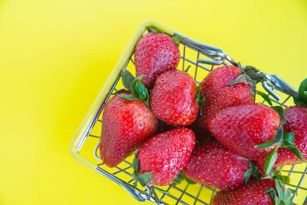 Zamknij się świeże truskawki z koszyka na jasnym żółtym tle. koncepcja reklamy świeżych produktów. skopiuj miejsce