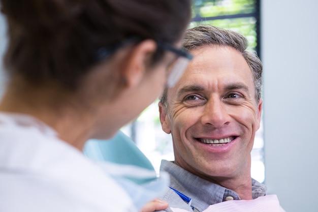 Zamknij się szczęśliwy pacjent patrząc na dentystę
