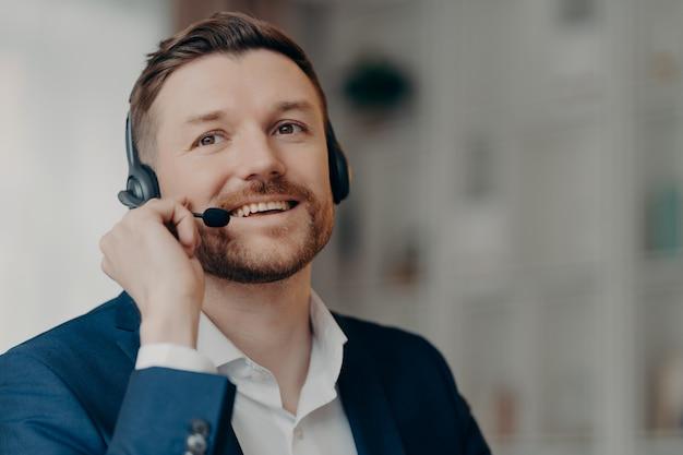 Zamknij się szczęśliwy pracownik biurowy przystojny mężczyzna call center operatora noszenia zestawu słuchawkowego i pracy w biurze, rozmawiając z klientem online z pozytywnym wyrazem twarzy, selektywne focus. praca i zawód