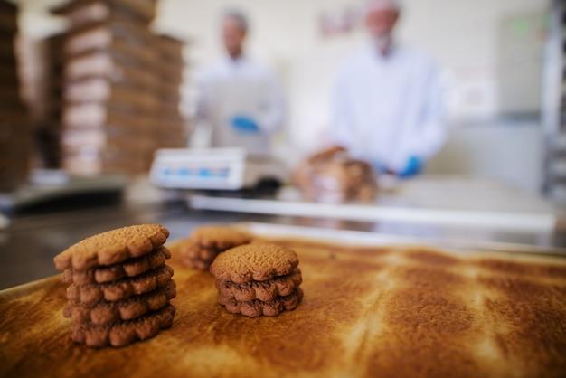 Zamknij się taca pełna świeżych ciasteczek pieczonych w fabryce żywności. zamazany obraz dwóch pracowników płci męskiej w sterylnych ubraniach w tle.