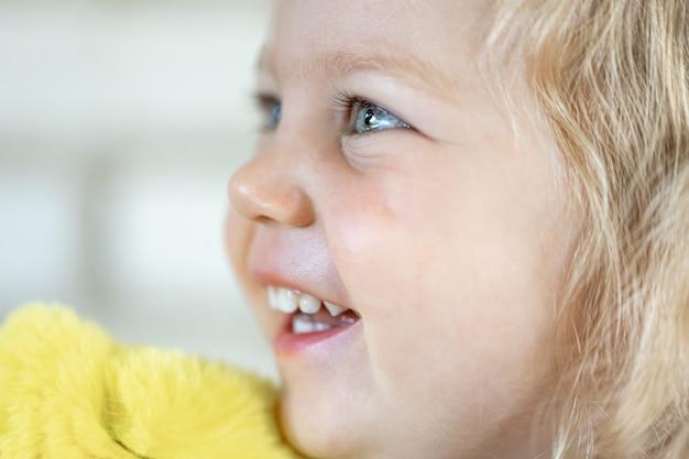 Zamknij się twarz trochę słodkie dziewczyny z dużymi niebieskimi oczami, uśmiechnięta dziewczyna.