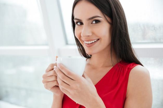 Zamknij się uśmiechnięta kobieta z filiżanką kawy stojącą w pobliżu okna w biurze i patrzącą na kamerę