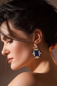 Zamknij się uśmiechnięta ładna pani pozowanie, pokazując projektant biżuterii. koncepcja piękna