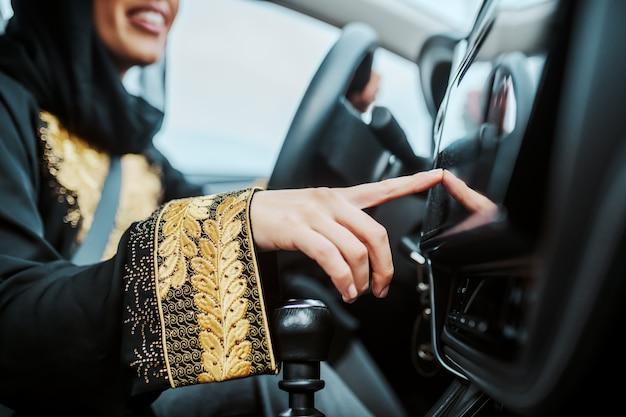 Zamknij się uśmiechnięta muzułmańska kobieta siedzi w swoim nowym samochodzie i włącza gps. selektywne skupienie się na dłoni.