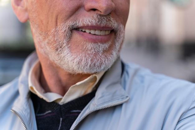 Zamknij się uśmiechnięty stary człowiek na zewnątrz