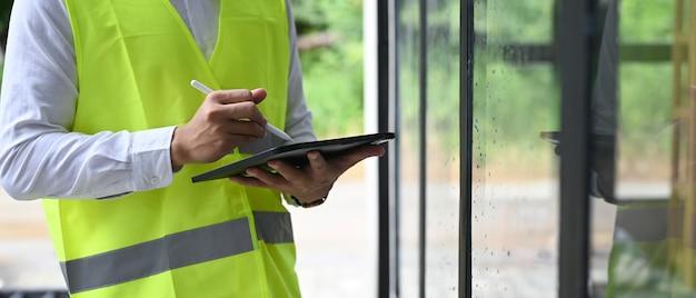 Zamknij się w budynku listy kontrolnej brygadzista z komputera typu tablet