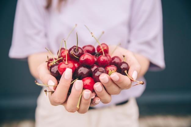Zamknij się w ręce kobiety trzymając czerwone wiśnie kolorowe