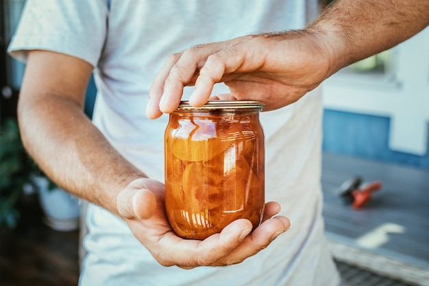 Zamknij się w ręce trzymając słoik dżemu brzoskwiniowego